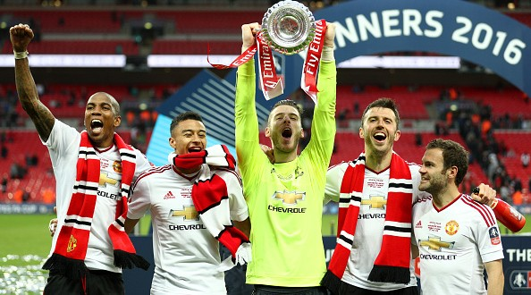 LONDON, ENGLAND - MAY 21:  (L-R) Ashley Young, Jesse Lingard, David De Gea, Michael Carrick and Juan Mata of Manchester United celebrate with the trophy on the pitch after The Emirates FA Cup Final match between Manchester United and Crystal Palace at Wembley Stadium on May 21, 2016 in London, England.  (Photo by Paul Gilham/Getty Images)