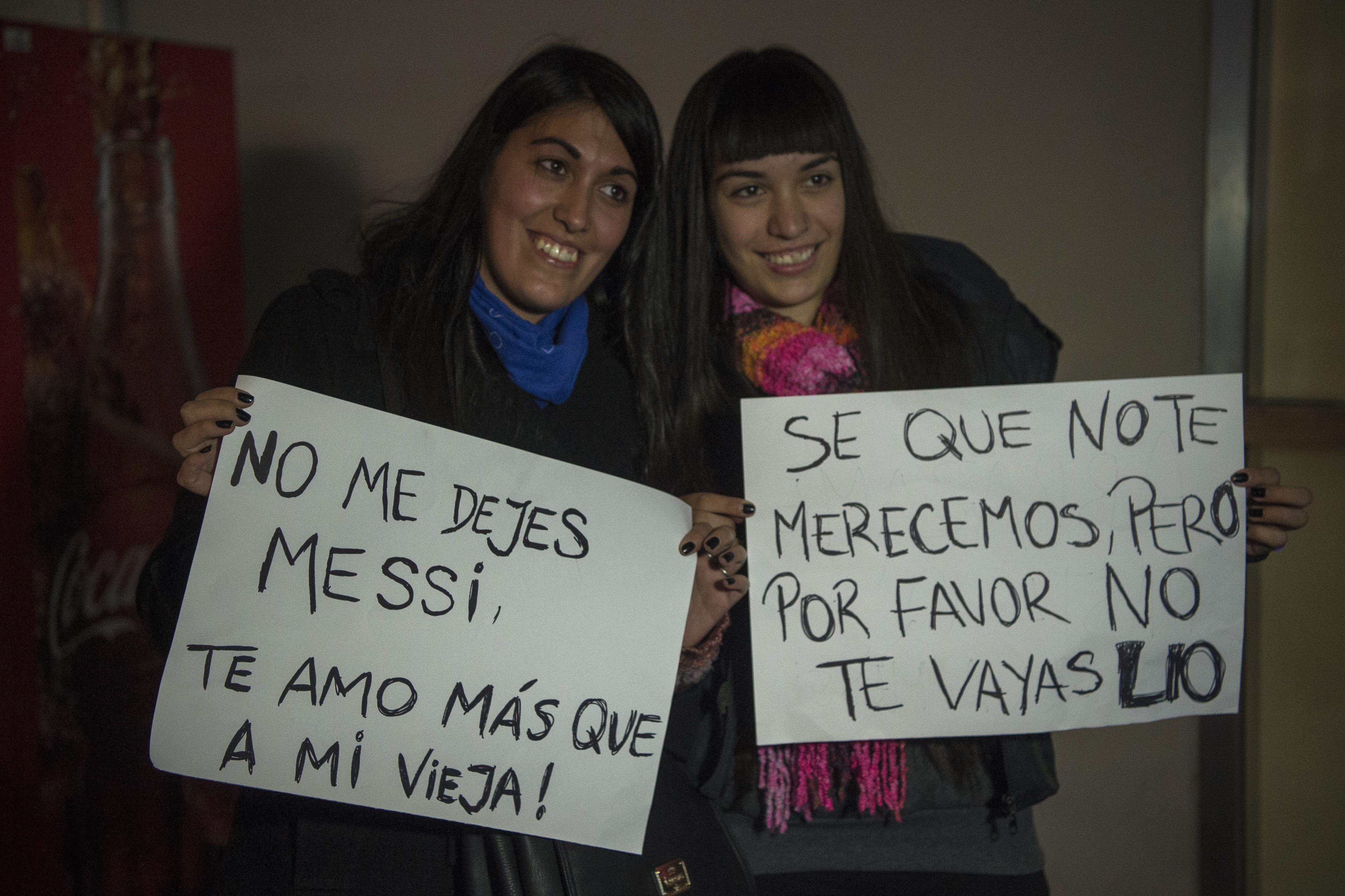 Two young women hold signs asking Lionel Messi no to quit, while waiting for the arrival of Argentina's football team from the Copa America Centenario held in the United States, on June 27, 2016 in Buenos Aires.  Argentina lost the final against Chile 4-2 in the penalty shoot-out. Argentines begged Lionel Messi -who tearfully decided to quit the international team after missing a spot-kick in the shootout- not to leave the national team despite its traumatic final. / AFP / EITAN ABRAMOVICH        (Photo credit should read EITAN ABRAMOVICH/AFP/Getty Images)
