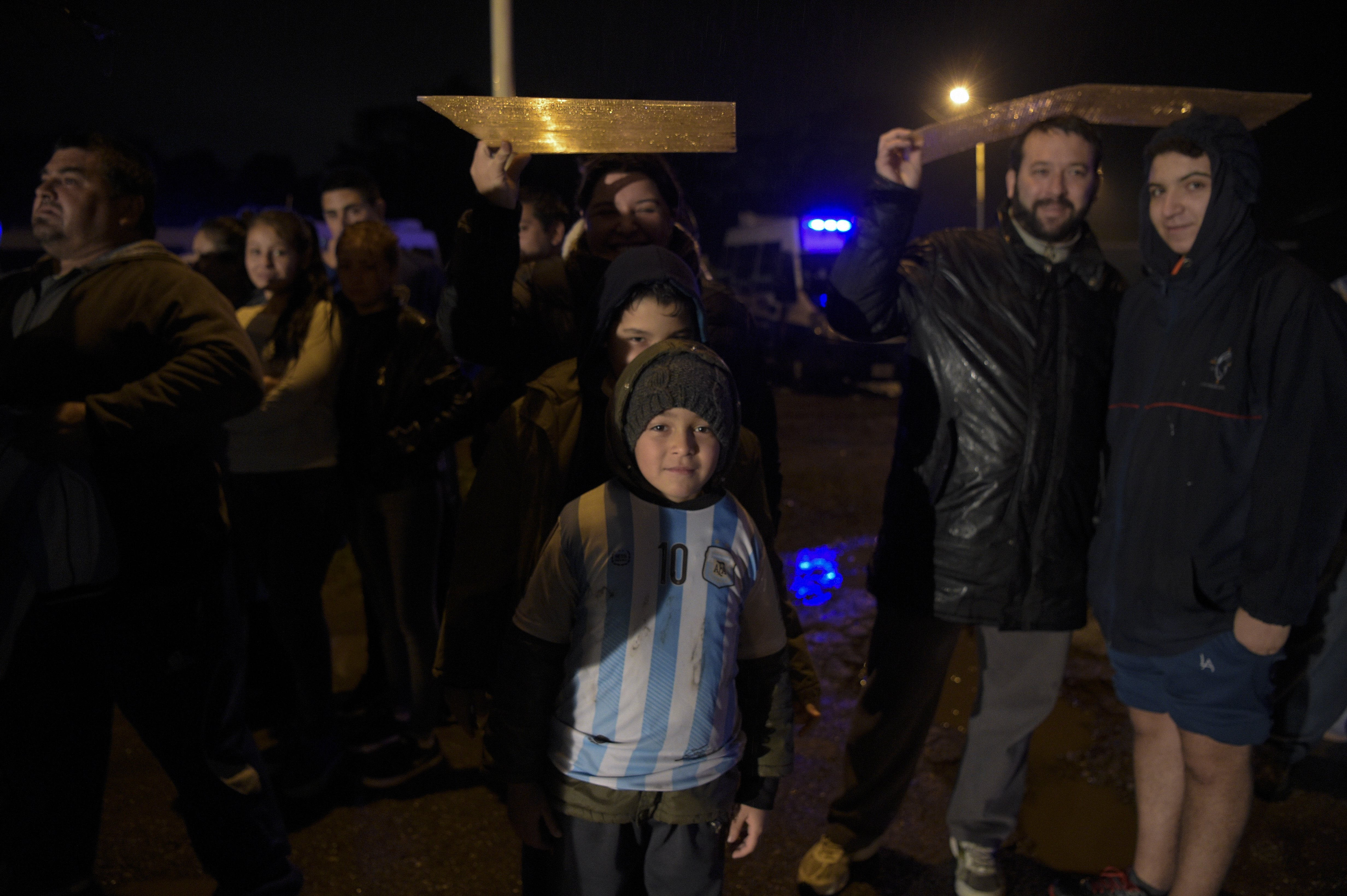People stand under the rain waiting for the arrival of Argentina's football team from the Copa America Centenario held in the United States, on June 27, 2016 in Buenos Aires.  Argentina lost the final against Chile 4-2 in the penalty shoot-out. Argentines begged Lionel Messi -who tearfully decided to quit the international team after missing a spot-kick in the shootout- not to leave the national team despite its traumatic final. / AFP / EITAN ABRAMOVICH        (Photo credit should read EITAN ABRAMOVICH/AFP/Getty Images)